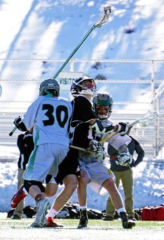 Take that: Summit's Dylan Lane (30) checks an Eagle Valley player during a home varsity lacrosse game in early April, caught in action by @louietraub