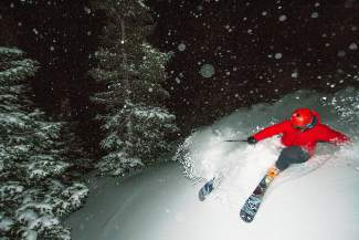 Georgetown skier Scott Wilkins slashes late-night powder at Loveland Pass on Christmas night, lit by a full moon that popped in and out of thick clouds.