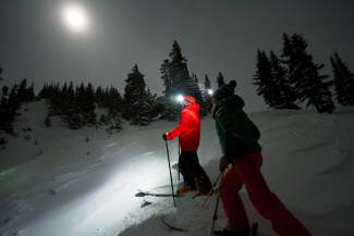 Skiers Scott Wilkins (left) of Georgetown and Dana Perry of Steamboat Springs prepare to drop a line under a full moon on Christmas night. The two brought headlamps just in case the moon was shrouded in clouds — and it was.