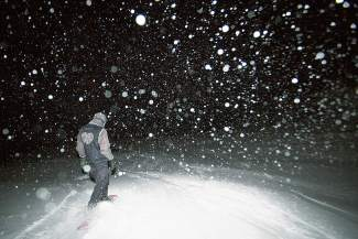 A snowboarder rides into the dark just as big, fat flakes start to fall during a full-moon trip at Loveland Pass on Christmas night, Dec. 25.