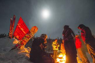 A collection of skiers and snowboarders crowd around a fire near the base of Loveland Pass on Christmas night, Dec. 25.