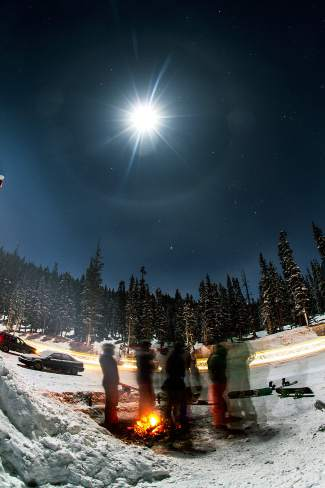 The final few skiers and snowboarders stick close to a dying fire at the base of Loveland Pass on Christmas night, Dec. 25. Near midnight, the clouds finally parted and the full moon started shining truly bright.
