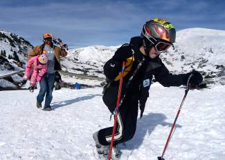 More than rail riding: 7-year-old Clay Smith (right) walks up a makeshift ski run while his dad, Will, acts as human chairlift for his younger sister, 4-year-old Bella, on Oct. 25 at Loveland Pass. Clay already had one day of skiing under his belt by then, and Will says his daughter couldn't wait to get out after driving over the pass a few days before.