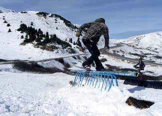 Tyler Rickenbacher, 25, holds a frontside boardslide on one of nearly a half-dozen rails and corrugated pipes at the top of Loveland Pass on Oct. 25.