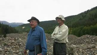 Bill Fountain (left) and Tom Waymire stand atop a dredge pile. Dredge boats would pull up, clean and discard rocks in the hunt for gold.