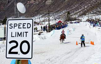 A horse-rider-skier team gallops and slides down an 800-foot course in downtown Minturn at the RMX Skijoring competition on Feb. 27. Horses reach 30-40 miles per hour as they navigate a course over jumps and around pylons while the skier collects rings around an old ski pole.