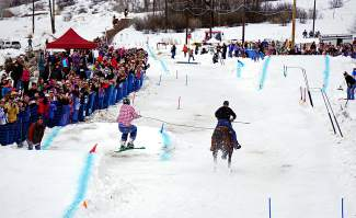 Skijoring competitors reach 30-40 mph as they navigate a course over jumps and around pylons, with skiers pulled along behind a horse.