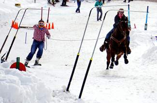 A skijoring skier reaches for rings to gather points during a competition in Minturn on Feb. 27.