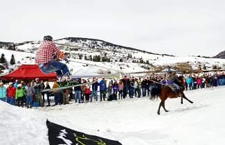 A skijoring competitor takes off from a jump while being towed by a horse and rider in Minturn on Feb. 27.