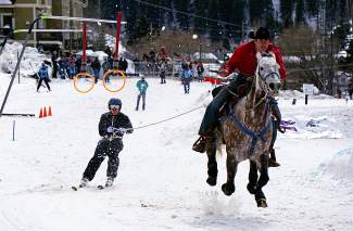 A skijoring team navigates a course filled with pylons, rings and jumps during a competition in Minturn on Feb. 27.