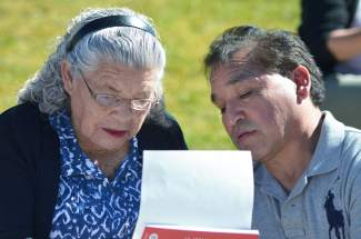 From left, 91-year-old Ernestina Rojas, a native of Mexico, examines her citizenship paperwork with her son Jorge Rojas after taking the Oath of Allegiance at Dillon Amphitheater on Oct. 8.