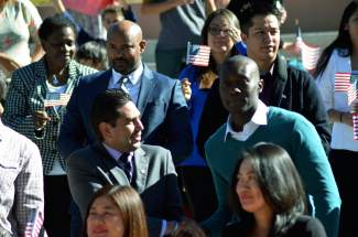 From left, Byron Rojas shakes hands with Nadim Quarshie after thye both became naturalized U.S. citizens on October 8.
