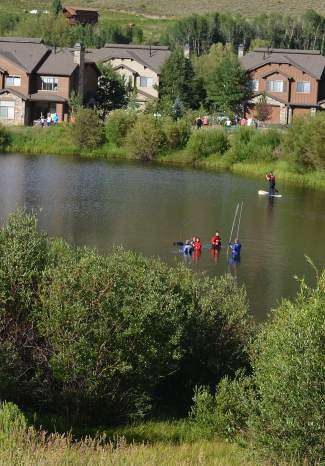 Members of Summit County's Search & Rescue Group used long poles to touch the bottom of North Pond in Silverthorne on Sunday evening, July 17, in search of a girl who reportedly drowned at the south end of the water while paddleboarding.