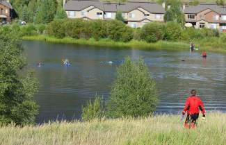 A member of Summit County's Search & Rescue Group looks on from one of the shorelines at Silverthorne's North Pond as other members of the team, including dog units, comb the water for a reported drowning victim Sunday evening.