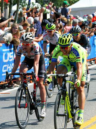 Fifth-place finisher Burno Pires (green) of Tinkoff-Saxo rides past fourth-place finisher Jonny Clarke (blue and white) of United Healthcare after crossing the USA Pro Challenge Stage 4 finish line on Main Street Breckenridge.