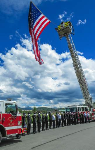 Members of the Red White and Blue and Lake Dillon Fire Departments stood at attention under a large American Flag honoring Patrick Mahany, as the procession approached Summit Medical Center.