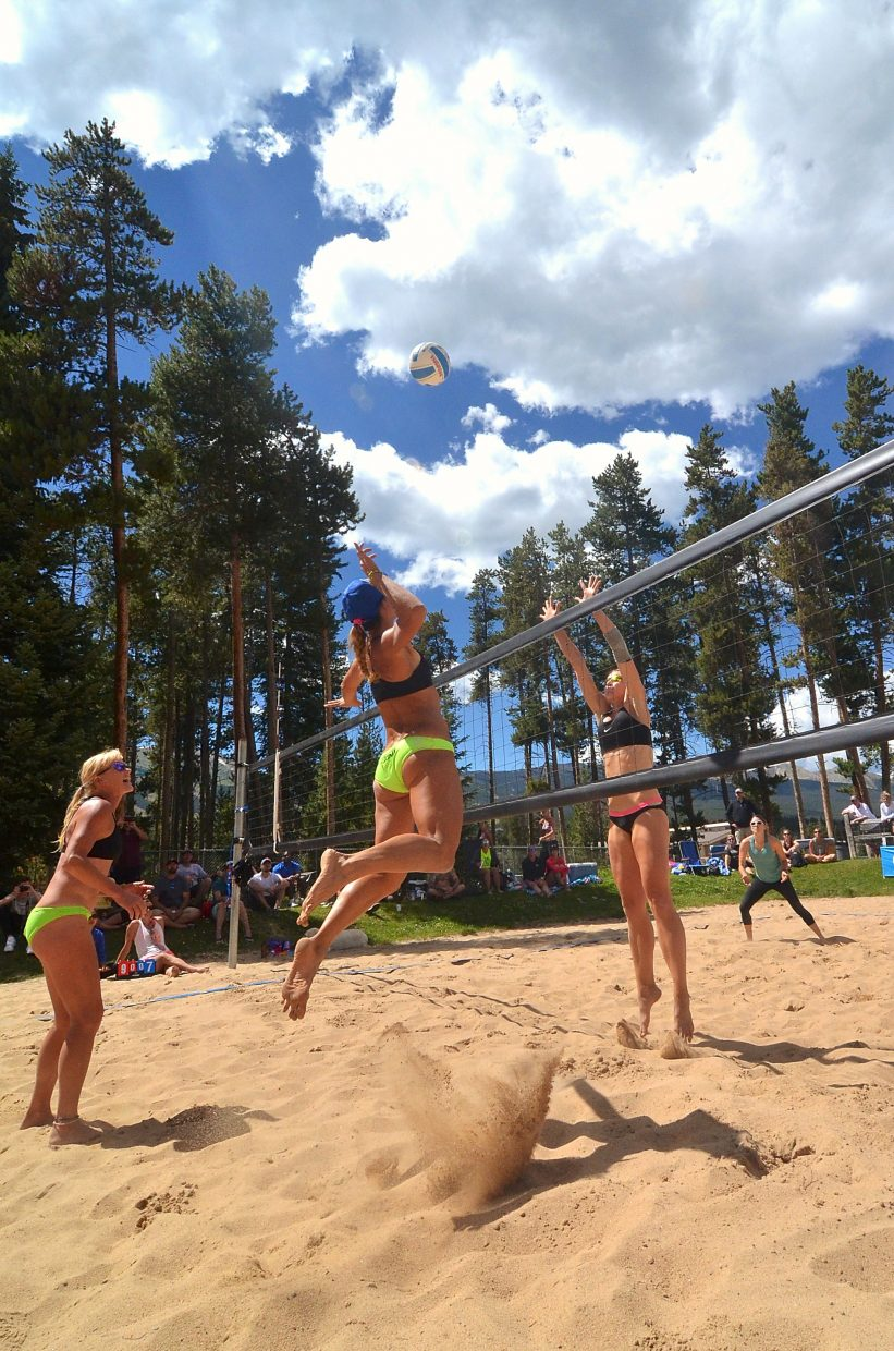 AVP pro and Colorado native Emily Stockman jumps for the spike and teammate Kris Bredehoft (left) guards while Denver opponent Katie Vatterodt (on net) goes for the block on the sand courts at Carter Park in Breckenridge during the annual Putterhead Doubles volleyball tournament on Aug. 13.