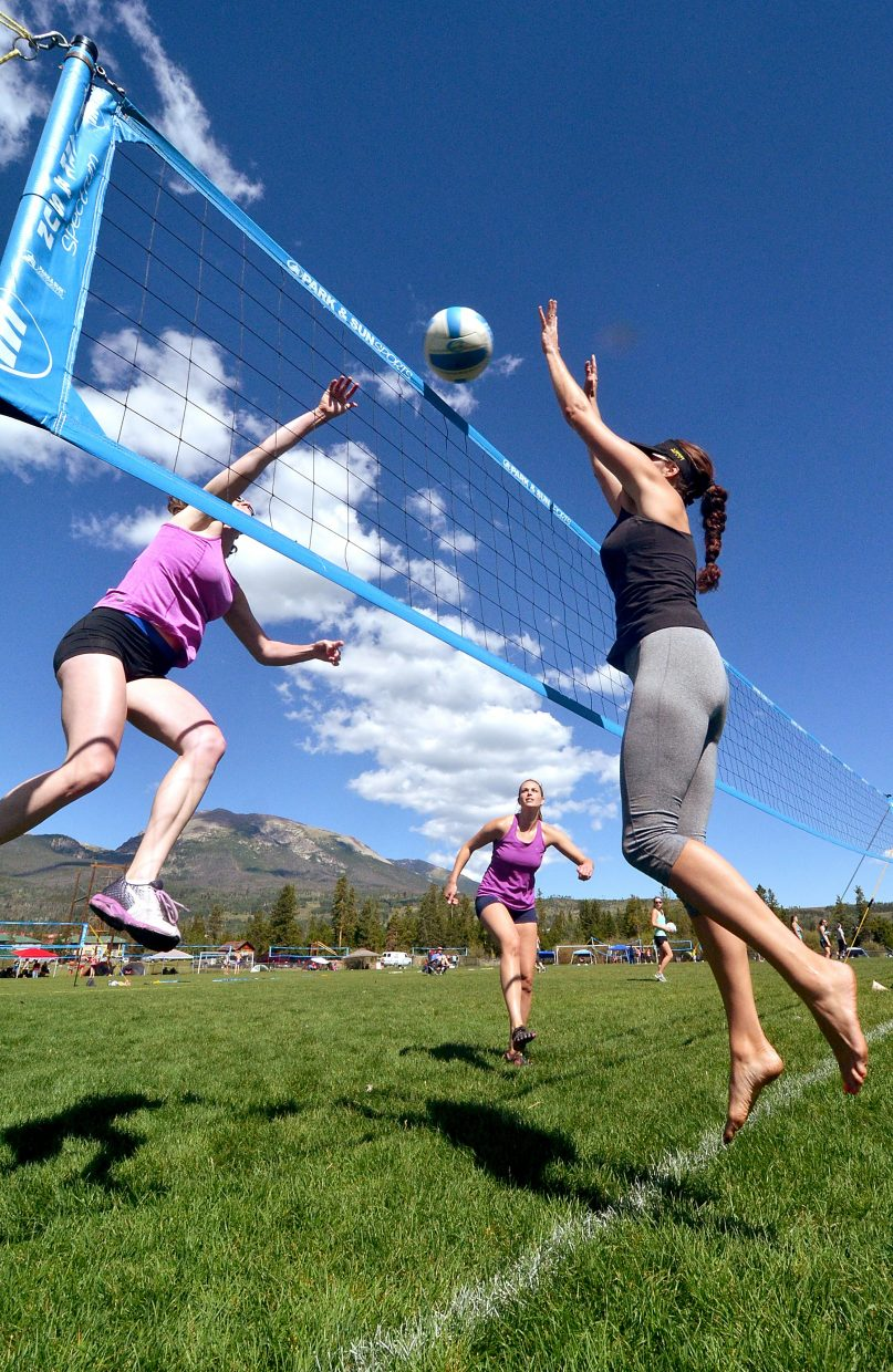 Kara Smith of Monument (left) goes for the kill with teammate Dana Krivanka (middle) while Kelly Pfannenstiel of Denver blocks on the grass courts at Frisco for the Putterhead Doubles volleyball tournament on Aug. 13.