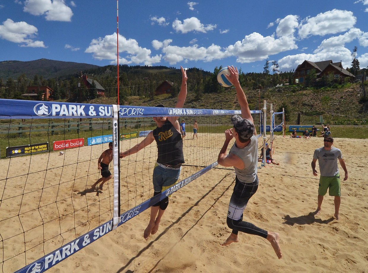 Brian Jones of Lakewood hits a spike into Matt Kuchar of Breckenridge as Dean Kuoni (left) and Kevin Mollman of Parker (right) stand guard on the sand courts at Silverthorne during the annual Putterhead Doubles volleyball tournament on Aug. 13.