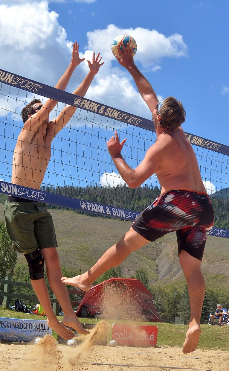 Sam Lambert (right) spikes the ball into a block from Mike Sauro of Minneapolis on the sand courts in Silverthorne during the annual Putterhead Doubles volleyball tournament on Aug. 13.