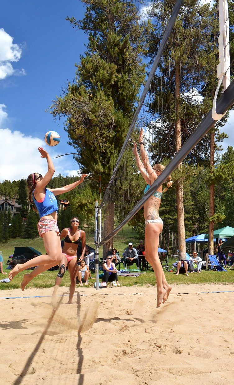 Mallory Deneen (left) of Denver goes for the kill while teammate Karina Goodwin guards and opponent Liz Card (right) jumps for the block on the sand courts at Carter Park during the annual Putterhead Doubles volleyball tournament on Aug. 13.