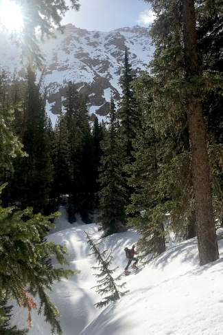 A skier ascends through trees to the base of the West Face of James Peak, a 13er found in the Arapahoe National Forest near St. Mary's Glacier.