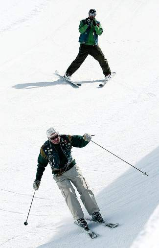 Ace McKee, background, films original Ravinos member John Faas, foreground, skiing through the halfpipe on the Ravinos St. Patrick's Day ski day in 2010.