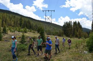 A small tour group consisting of members of Summit County government, the U.S. Forest Service and Great Outdoors Colorado (GOCO) passes under overhead power lines along the county's proposed Fremont Recpath on Monday, June 20.