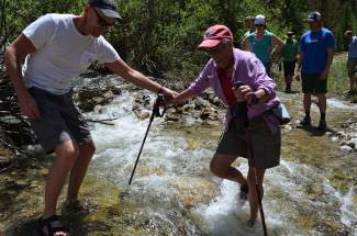 County Commissioner Thomas Davidson assists Patricia Taylor, a Continental Divide Land Trust board member, across one of a handful of small stream crossings along the proposed Fremont Recpath on Monday, June 20.