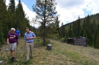 Among a small tour group, Todd Rankin, a volunteer for Summit County Open Space & Trails, and Great Outdoors Colorado (GOCO) executive director Jim Spaanstra pass by a dilapidated cabin along the county's proposed Fremont Recpath on Monday, June 20.