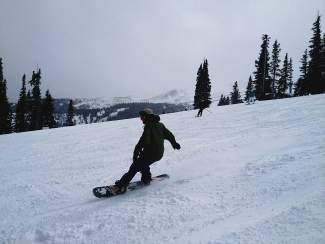 A snowboarder enjoys new snow on Peak 8 after a spring storm during last year's closing day at Breckenridge Ski Resort.