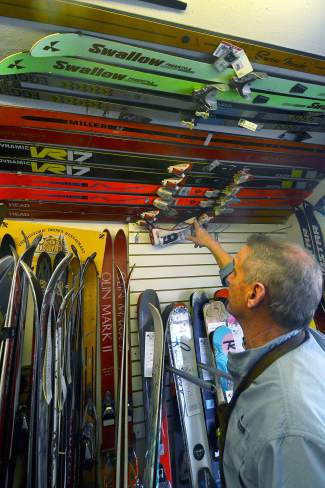 Pup Ascher points to skis, ski passes and photos on the Dead Man's Wall at his Breckenridge ski shop. It's a tribute to close friends and locals he's known through the years who have died, whether from skiing or cancer or suicide.