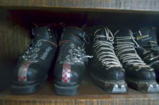 Vintage ski boots in Pup Ascher's living room, stowed beneath a flatscreen TV next to a sparkling Christmas tree. (It was mid-day in the hectic week between Christmas Day and New Year's.) The boots pair with six pairs of skis next to the couch on the next wall.