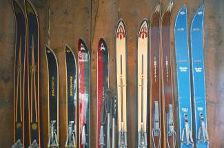 Vintage skis against the living room wall in Pup Ascher's 1885 cabin just outside of Breckenridge. The skis in his living room span four decades, from the 1940s (a pair of 10th Mountain Division skis, not pictured) to the 1970s.