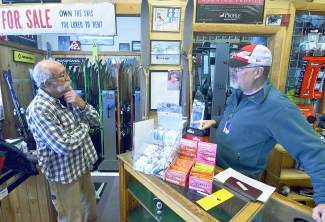 Jimbo Deines (left) of Precision Ski and Golf talks vintage ski gear with client Nail Gallaway of Frisco. The two are standing in front of '40s-era German army skis Deines got from another client, Hans Bucklitzsch, who also left a note explaining how he came to own the skis before leaving East Germany in 1948. Gallaway found two similar pairs at a garage sale in Michigan, but his didn't come with the original bindings.