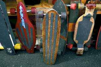 A sampling of Jim Bowden's vintage skateboards, including handmade decks modified with purloined roller-skate wheels.