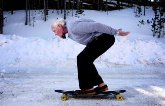 Jim Bowden on the snow with a longboard from his collection. Bowden brought skateboards from California to Summit County in the late 1960s and still has more than a dozen original models.