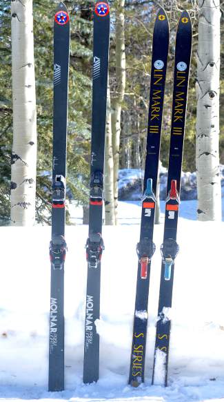 Two pairs of vintage powder skis from the '70s: Molnar Prism Lights (left) with Marker bindings and Lin Mark III S Series (right) with mismatched Look Nevada turntable bindings. The models are from the same era when other early powder skis (The Ski, Miller Softs) were flooding the market.