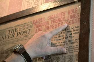 Mike Cavanaugh of the Brown Hoetl in Breckenridge points to headlines on newspaper clippings he discovered in the floorboards during renovations on the 150-year-old building. The majority of clippings came from the Spanish-American War, World War I and World War II.