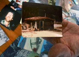 Peter Dunn with a photo of his one-room cabin in Montezuma, the first place he lived when he moved from Los Angeles to Summit County in 1977. Two years later, just after Arapahoe Basin closed in the spring of 1979, he moved to Bavaria for two years of ski bumming around Europe.