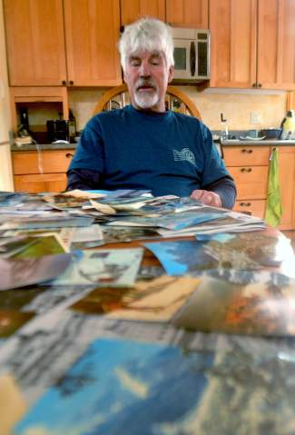 Peter Dunn looks over dozens of vintage photos and ski maps in his kitchen just outside of Frisco. Over the years, he's collected photos from his adopted hometown of Summit County, Europe, Canada and more, including faded images from naked hot-tubbing in Bavaria.