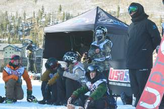 A group of snowboarders watches during the second run at the Revolution Tour halfpipe qualifier on Dec. 2 at Copper Mountain.