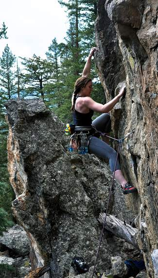 Local climber Brigitte Coburn begins her ascent of Equilibrium, a 5.9+ route at Alpenglow Wall outside of Keystone. The tucked-away spot offers several sport climbing routes.