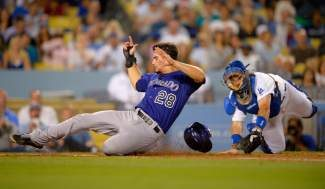 Colorado Rockies' Nolan Arenado scores under the tag of Los Angeles Dodgers catcher A.J. Ellis on a single by DJ LeMahieu during the fifth inning of their baseball game, Friday, July 12, 2013, in Los Angeles. (AP Photo/Mark J. Terrill)