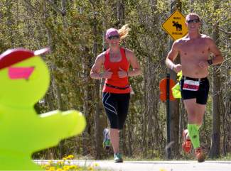 A duo of runners passes by street signs and moose warnings in the last leg of the half marathon at the 2016 Run the Rockies road race from Copper to Frisco on June 4. The 40th anniversary of the June 10K and half marathon drew more than 400 runners from across Colorado and the West.