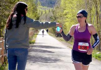A volunteer hands water to runners competing in the half marathon at the 2016 Run the Rockies from Copper to Frisco on June 4. The 40th anniversary of the June 10K and half marathon drew more than 400 runners from across Colorado and the West.
