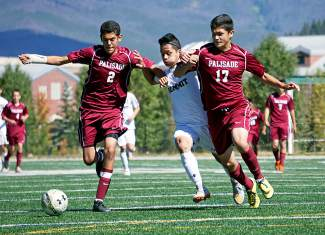 Summit High's Gerson Martinez, center, battles for position with Palisade's Eric Payan (2) and Bryan Franco-Perez (17) during the first half of a varsity soccer game in Summit on Sept. 19. The Tigers would go on to win 3-0.