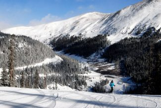 Wildernest resident Cheri Breeman stands out against a splendid backdrop as she stops briefly while skiing Ramrod at Arapahoe Basin Tuesday morning. Several inches of new snow covered the central mountains after Monday's storm with more snow predicted throughout the rest of the week.