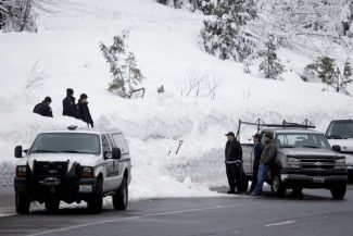 King County Sheriff's officers and other emergency officials work along Highway 2 near Stevens Pass ski resort in Skykomish, Wash., near where three skiers were killed in an avalanche Sunday, Feb. 19, 2012. The avalanche swept the three skiers about a quarter-mile down an out-of-bounds canyon at the popular resort. A fourth skier caught up in the slide was saved by a safety device, authorities said. (AP Photo/The Seattle Times, Erika Schultz)  MAGS OUT; NO SALES; SEATTLEPI.COM OUT; MANDATORY CREDIT