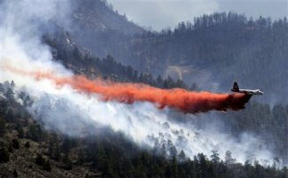 A slurry bomber drops retardant on the Lower North Fork Fire in Jefferson County, Colo., Tuesday, March 27, 2012. Investigators were trying to determine whether a controlled burn designed to minimize wildfire risk reignited and became a stubborn mountain wildfire that forced hundreds of residents to flee their homes and may have caused the deaths of two people. (AP Photo/The Denver Post, RJ Sangosti)